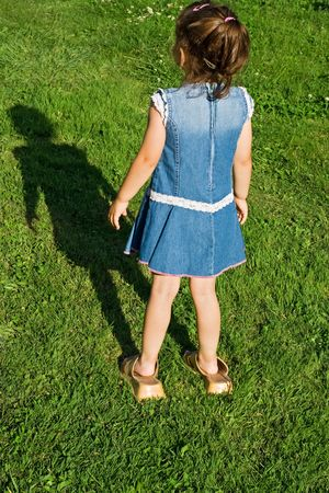 Little girl wearing her motherss slip-on and staying on the green grass Stock Photo