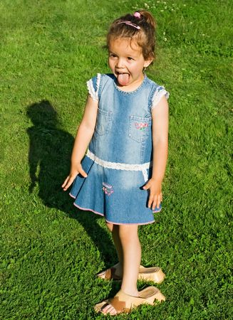 clasp feet: Playful little girl putting her tongue out and wearing mothers slip-on