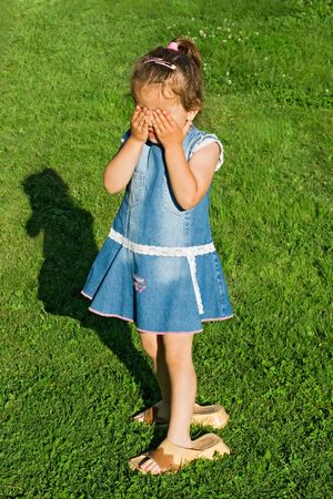 clasp feet: Playful little girl wearing slip-on and playing hide-and-seek Stock Photo
