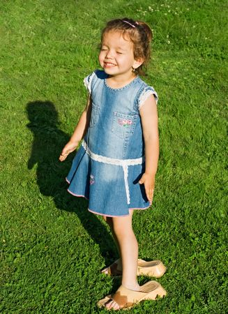 Smiling little girl closing her eyes and wearing mothers slip-on