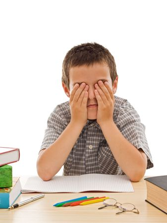 Tired schoolboy covering his eyes - isolated