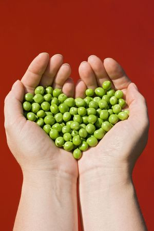 Womans hands holding green peas on red background