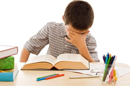 School boy reading from an old book and covering his face Stock Photo