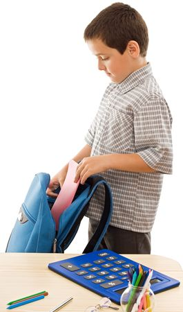 Schoolboy putting an exercise book in a blue color schoolbag - isolated Stock Photo