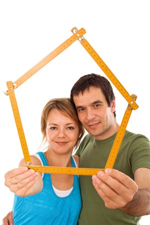 Young couple with model house of wooden meter - isolated photo