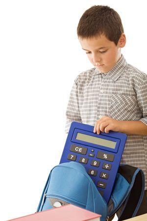 Schoolboy putting a calculator in a blue color schoolbag - isolated Stock Photo