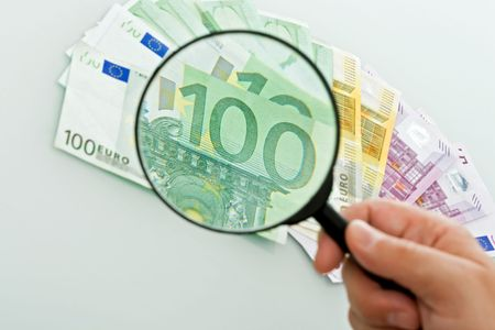 Hand holding a magnifying glass for better viewing of the banknotes