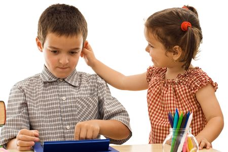 Little girl holding the schoolboy by the ear - isolated Stock Photo