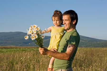 Father and his girl walking on the meadow in  summer day