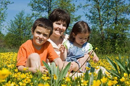 Beautiful woman with her happy children sitting among yellow flowers photo