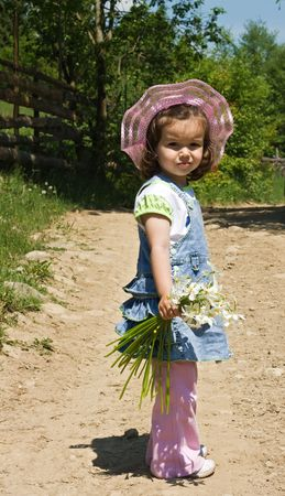 Little girl with flowers in her hand walks on a country lane