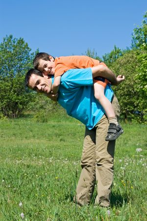 Happy father and his smiling son playing outdoors Stock Photo