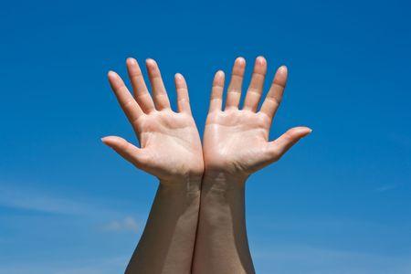 Open womans hands against blue sky