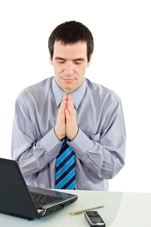 Businessman praying for success Stock Photo