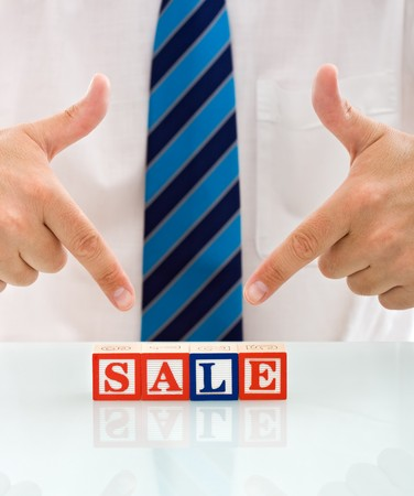 Businessman pointing to the blocks, sale concept