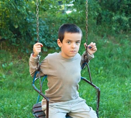 Little boy swinging in the garden