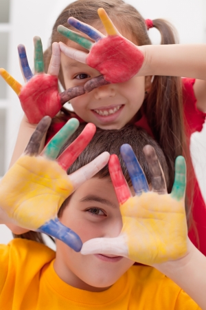 Children making funny face with their colored hands