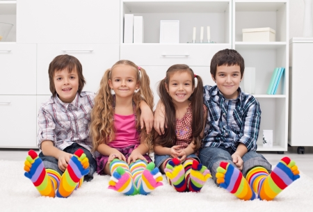 Happy children sitting on the carpet wearing colorful socks Stock Photo