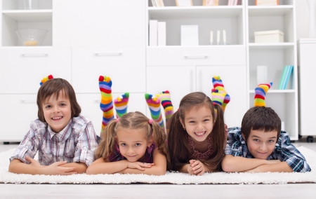 black toes: Children laying on the floor wearing colorful socks Stock Photo