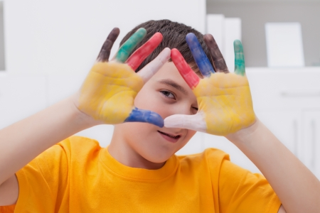 Little boy making funny face with his colored hands Stock Photo