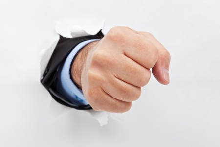 Businessman's fist punishing through paper photo