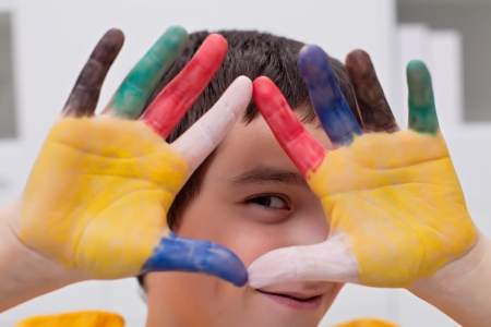 Happy boy making funny face with his colored hands Stock Photo