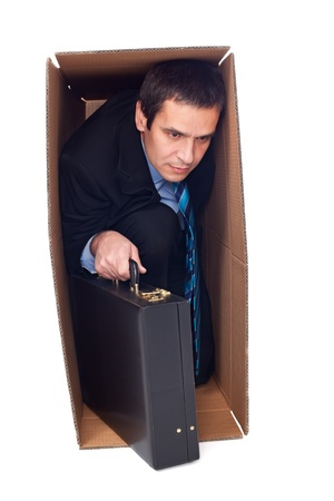 Businessman with briefcase is inside of a cardboard box - way out for the solution