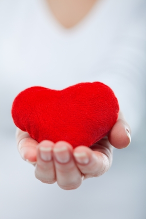 Woman keeping red heart in her palm Stock Photo