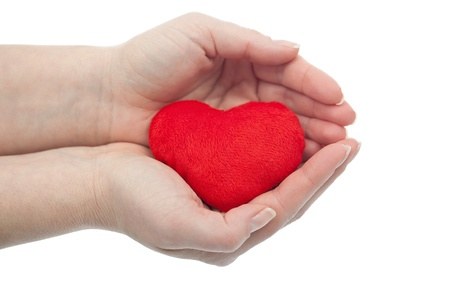 Woman palms protecting red heart - health or love concept Stock Photo