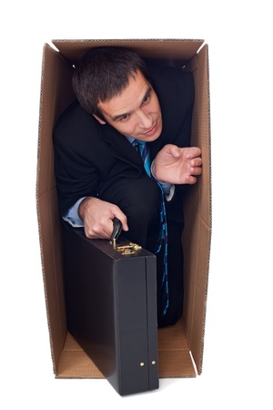Businessman with briefcase inside of a cardboard box