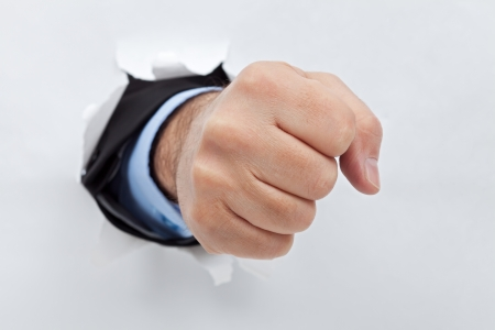 Powerful businessman's fist punishing through paper photo