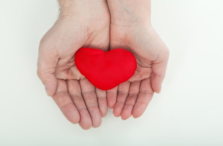 Couple holding a red heart in their palms