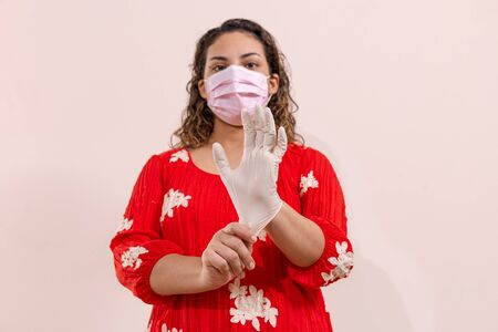 Latin woman taking precautions by covid-19 wear a face mask, gloves and sprayer to prevent infection