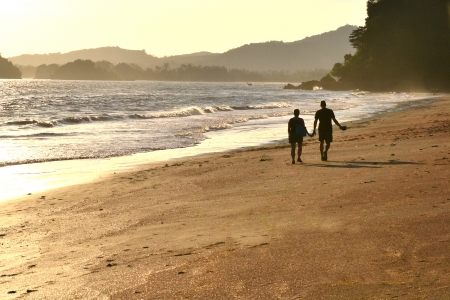 Couple walking along beach at sunset, Krabi, Thailand photo