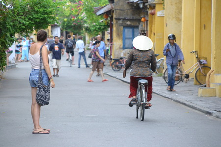 non la: Local Cyclist in non la traditional hat and tourist in Hoi An, Vietnam