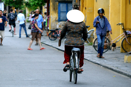 non la: Local Cyclist in non la traditional hat in Hoi An, Vietnam