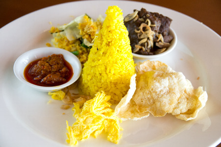 sambal: Nasi Kuning Indonesian yellow rice served with braised beef, shredded egg, vegetables, coconut salad, homemade sambal and crackers.