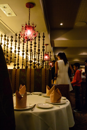 Table setting with napkins in Indian restaurant and hanging lights Editorial