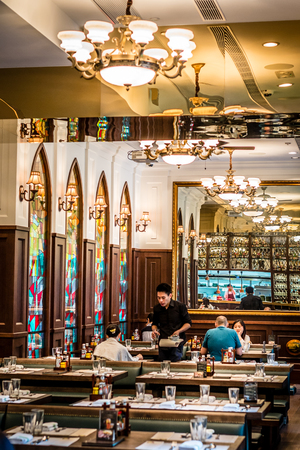 European bistro interior with table settings and chandeliers and stained glass