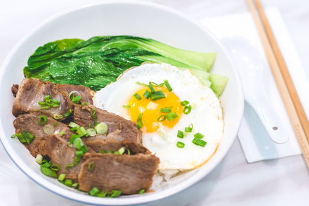 Porky Bowl Homemade char siu with rice and sunny side up & siew pak choy Stock Photo