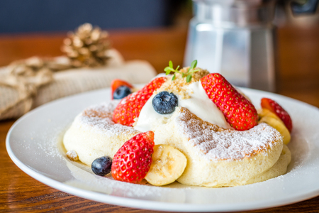 Fruit Salad Souffle Pancake with fresh strawberry, berry, banana, whipped cream and maple syrup