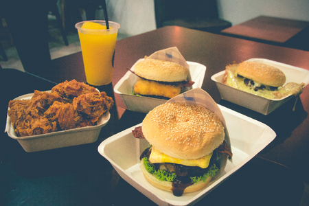 a variety of fast food hambuger fried chicken iced orange slush