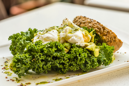 Crushed avocado, lemon, olive oil, two poached eggs and fresh kale on wholemeal sourdough, with kale and basil pesto. Standard-Bild