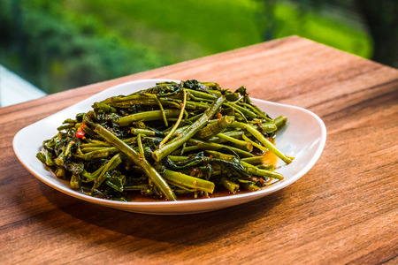 Stir fry sambal chilli kang kong vegetable served in a white porcelain dish