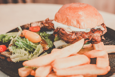 Grilled brioche burger with chef creation soya sauce chicken, lettuce, tomatoes, monterey cheese, mixed salad with olive oil vinagrette and french fries
