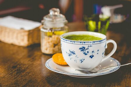 green tea matcha soy latte in a china cup with brown sugar and a glass of water on the side Stock fotó