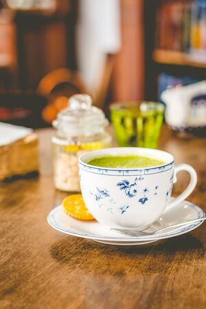 green tea matcha soy latte in a china cup with brown sugar and a glass of water on the side