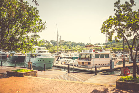 Luxury yachts parked at a seaside yacht berth at Sentosa Cove, Singapore
