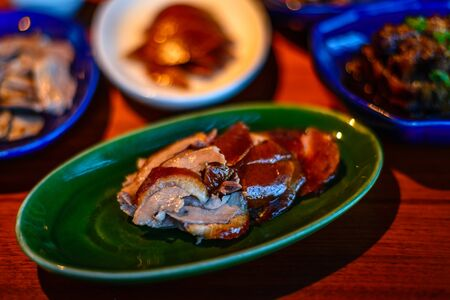 Chopped roasted duck with crispy skin presented on a green plate