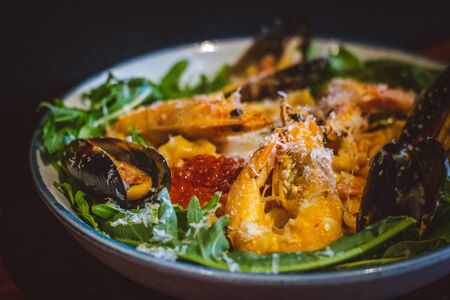 Pink sauce pasta (a mixture of Pomodoro and Carbonara), Grated Parmesan, Extra Virgin Olive Oil, Arugula, Sous Vide Egg, Calamari, Black Lump Fish Caviar, Black Truffle Pate, Prawns 写真素材
